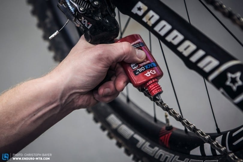 Cleaning the chain on a mountain bike.